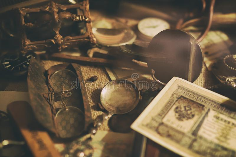Banknotes and coins of the Russian Empire, glasses in a case, silverware. Different antique items on the table: bronze jewelry, banknotes and coins of the royalty free stock image