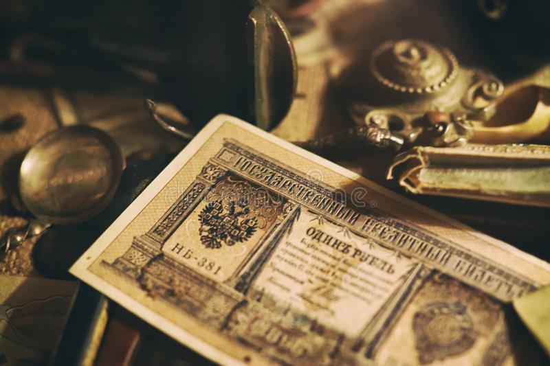 Banknotes and coins of the Russian Empire, glasses in a case, silverware. Different antique items on the table: bronze jewelry, banknotes and coins of the stock image