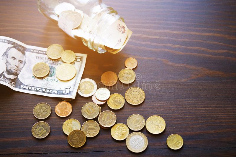 Banknotes, dollars, and coins of different countries on the background of a wooden table. Next to the glass jar with the stock photo