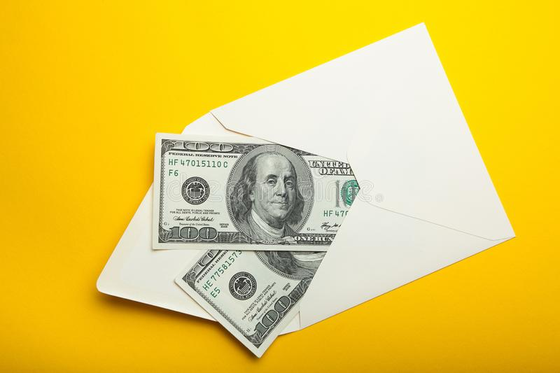 Banknotes in envelope, money in finance concept, isolated in yellow background.  stock image