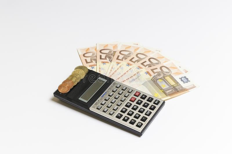 Banknotes, euro coins and a calculator stock photography