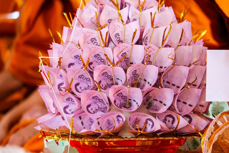 Banknotes are finely folded to decorate on the golen plate to give to the Buddhist temple stock images