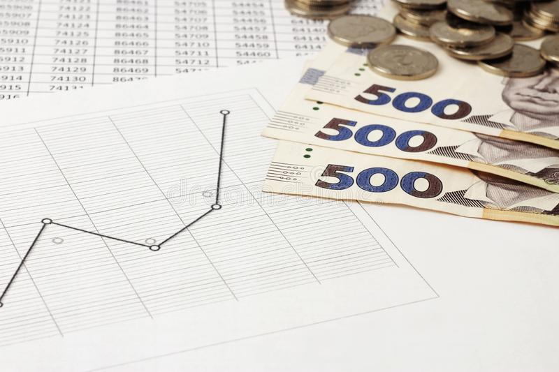Banknotes of 500 hryvnias, coins, Ukrainian hryvnia, with a face value of 2 hryvnias are on tables and graphs. The concept of money growth, profit and capital royalty free stock images