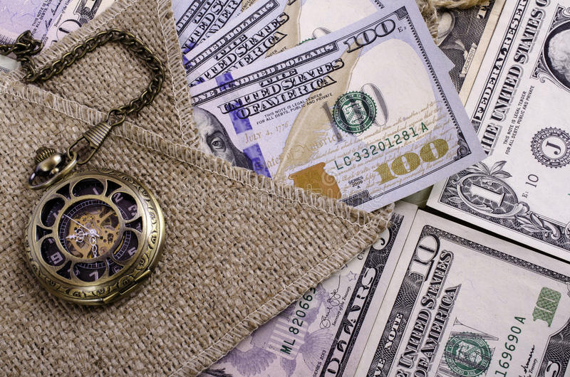 Banknotes hundred dollars and other denomination, burlap and pocket watches. stock photo