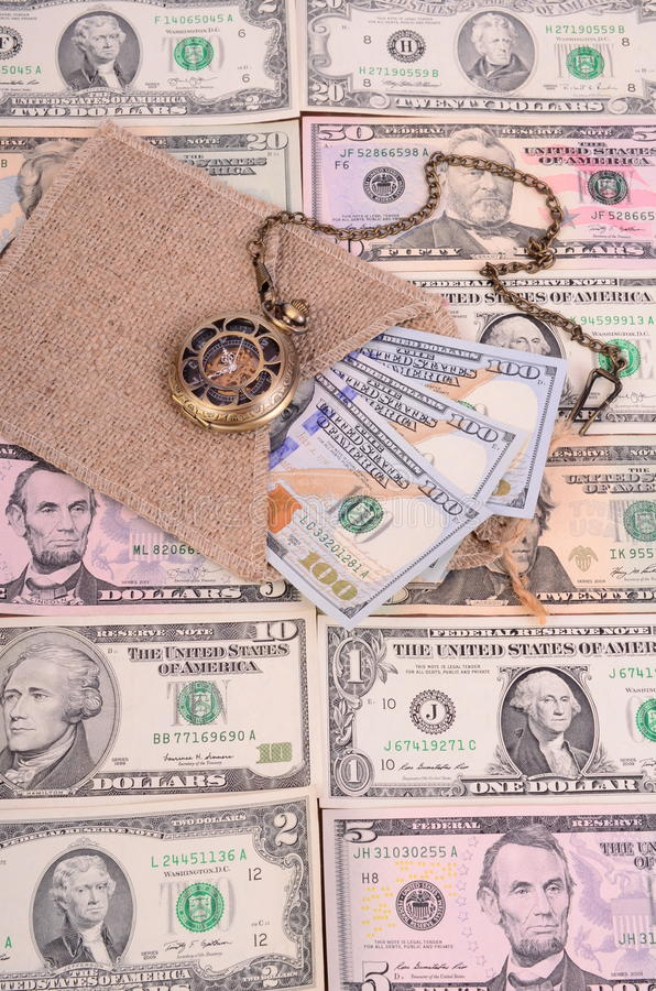 Banknotes hundred dollars and other denomination, burlap and pocket watches. royalty free stock image