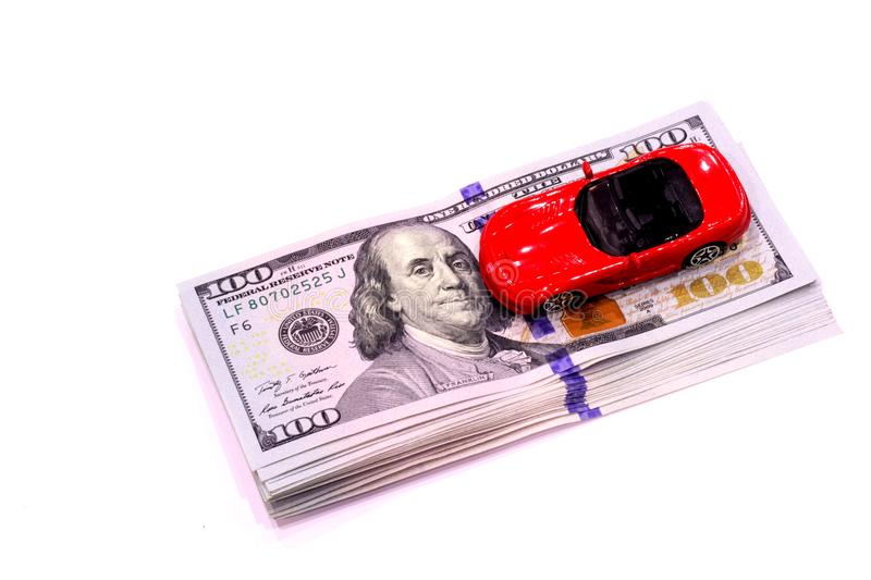 Banknotes and a red sports car. One hundred dollars banknotes and a red sports car royalty free stock images