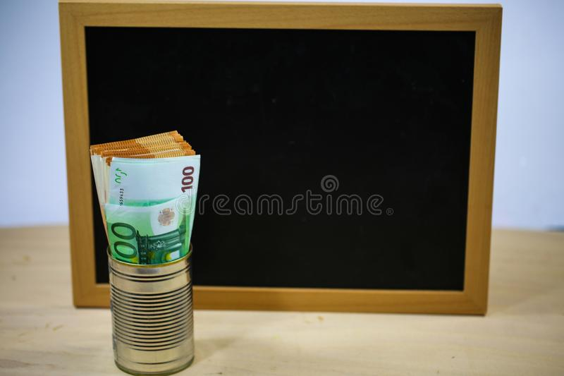 Banknotes in a tin can with chalkboard in the background, donations stock image