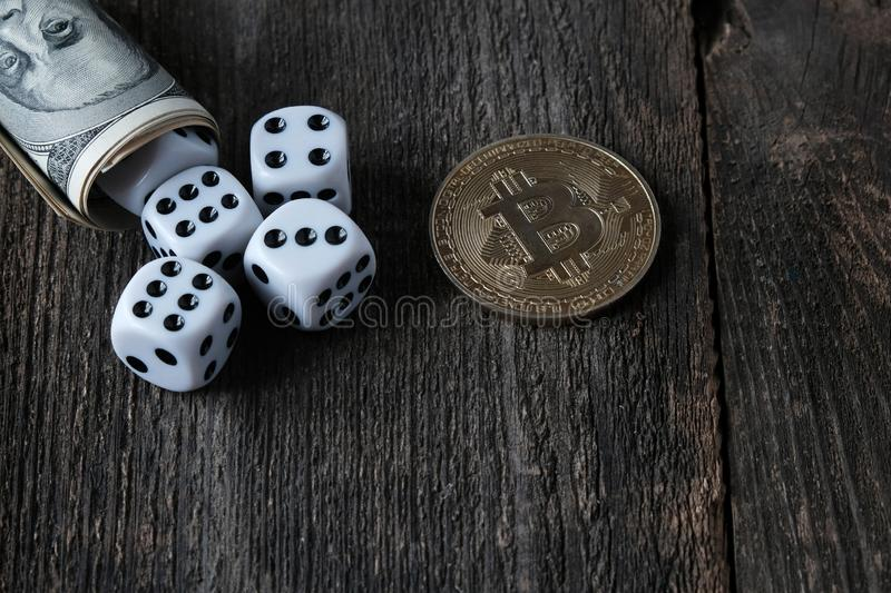 Banknotes of US dollars, bitcoin coin and dice. Concept of cryptocurrency stock image