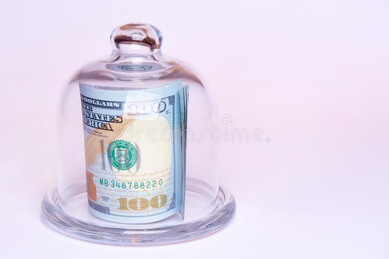 Banknotes worth one hundred dollars under a glass dome on a white background. Copy space. Banknotes worth one hundred dollars under a glass dome on a white stock photo