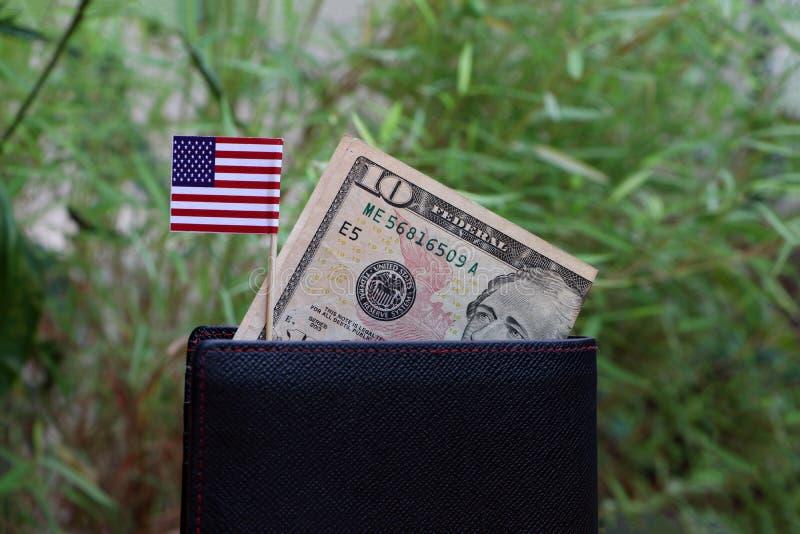 Banknotu pieni?dze dziesi?? dolar ameryka?ski i mini Ameryka zaznaczamy na czarnym portflu z zielonym natury t?em fotografia royalty free
