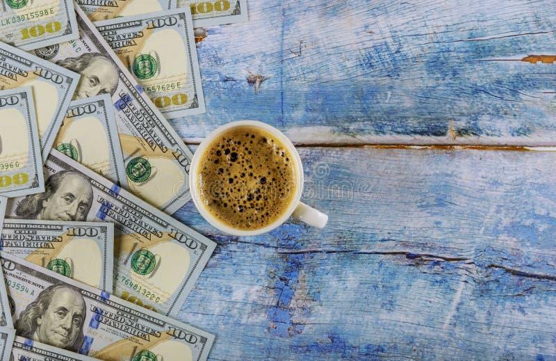 Banknoty dolara amerykańskiego i kubek czarnej kawy na rustycznym stole, widok z góry obrazy royalty free