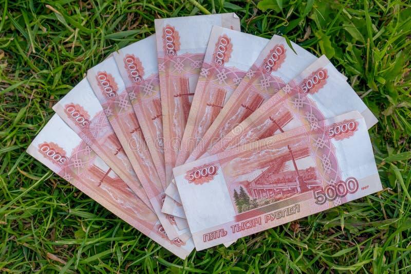 Banknoty 5.000 Rosyjskich rubli na trawy zieleni tle rosyjskie ruble pieni?dze obraz stock