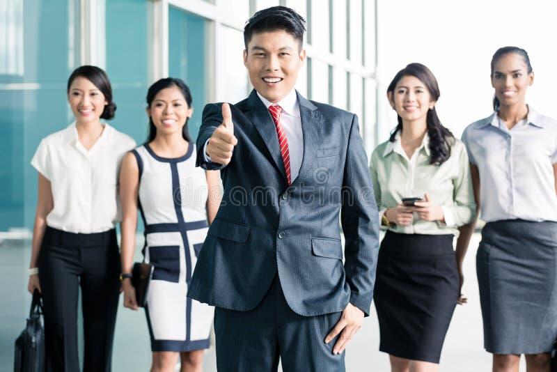 Bankpersonal vor dem Büro, das sich Daumen zeigt lizenzfreie stockfotografie
