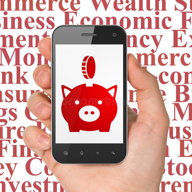 Bankrörelsebegrepp: Räcka hållande Smartphone med sparbössan med myntet på skärm royaltyfri bild