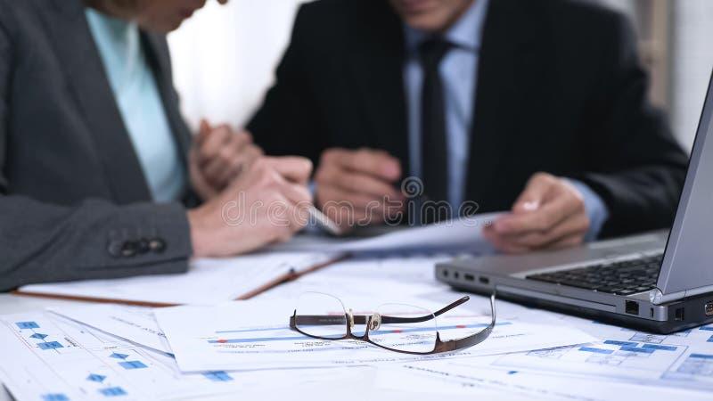 Bankrepresentanter som analyserar statistik, anmäler finansiella diagram, skrivbordsarbete royaltyfria bilder
