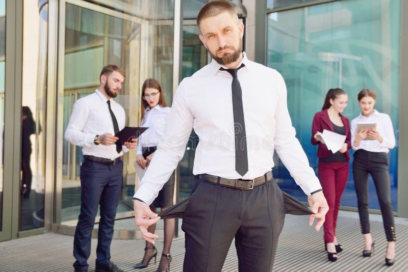bankrott Ein junger Mann in der schwarzen Hose und in den Dämonen eines Weißhemdes lizenzfreies stockbild