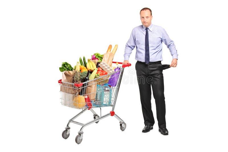 Bankrotter Mann, der einen Einkaufswagen anhält stockbilder