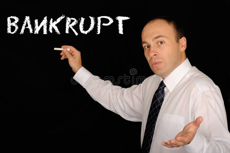 Bankrupt. Man writing the word Bankrupt on a blackboard stock photo
