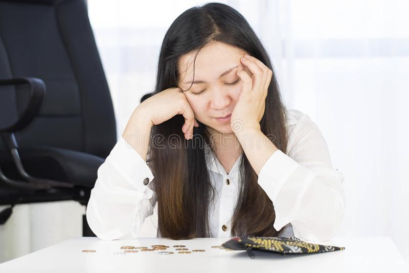 A bankrupt, broke and frustrated woman is having financial problems with coins left on the table and an empty wallet. stock photo