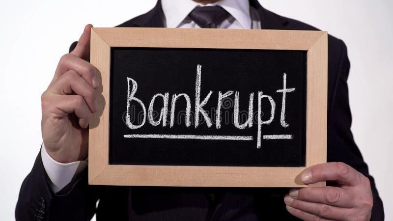 Bankrupt escrita no quadro-negro nas mãos do homem de negócios, na perda de dinheiro e na propriedade fotografia de stock