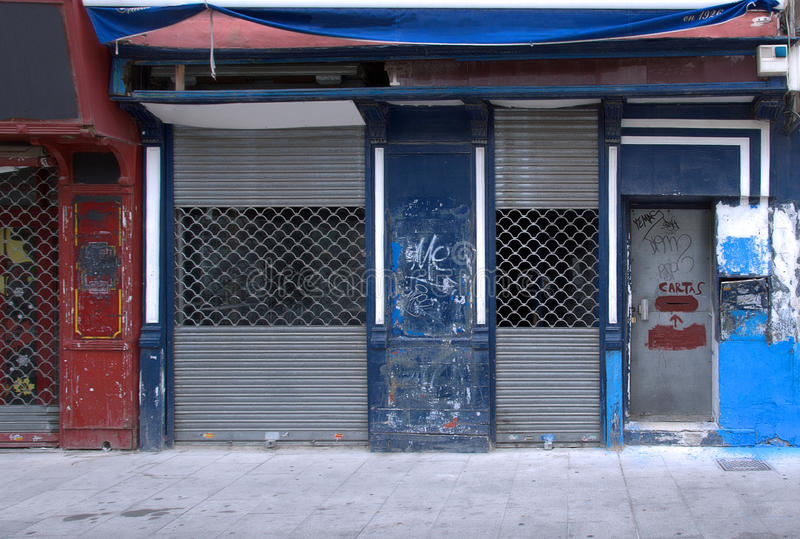 Bankrupt shop. Storefront of a bankrupt small shop, with a closed rolling shutter royalty free stock photo