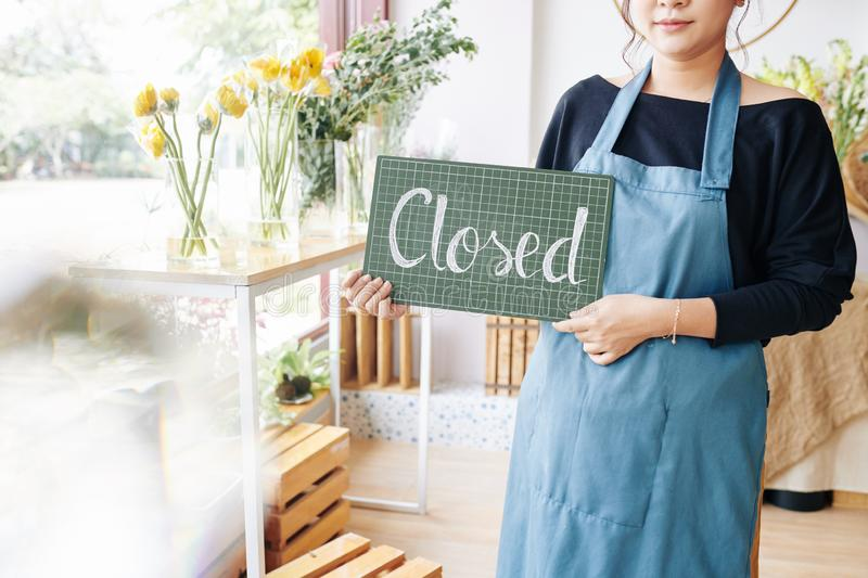 Woman closing flower shop stock images