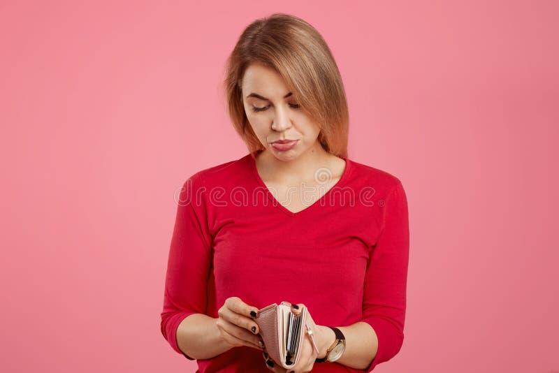 Bankruptancy和财务概念 生气的可爱的女性看与在钱包的不快乐的表示,没有金钱和许多债务 库存照片