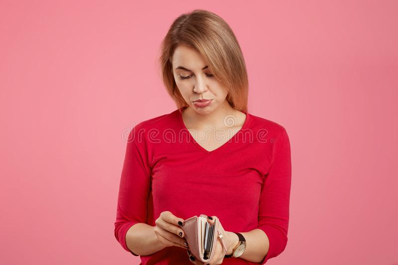 Bankruptancy and finance concept. Displeased attractive female looks with unhappy expression in purse, has no money and many debts stock photos