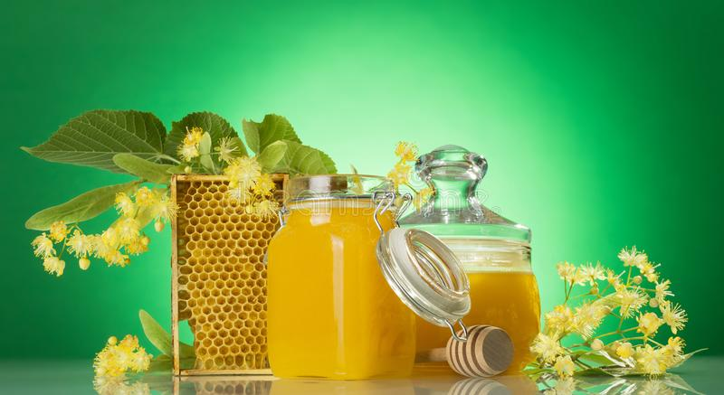 Banks with honey, honeycomb, wooden spindle and Linden flowers on green stock image