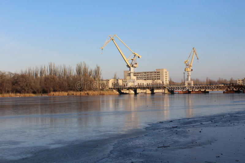On the banks of the river are large cranes. This plant builds ships. royalty free stock images