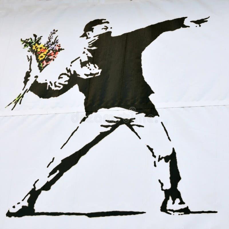 Banksy Stück eines Aufständischers, der einen Blumen-Blumenstrauß wirft lizenzfreies stockbild