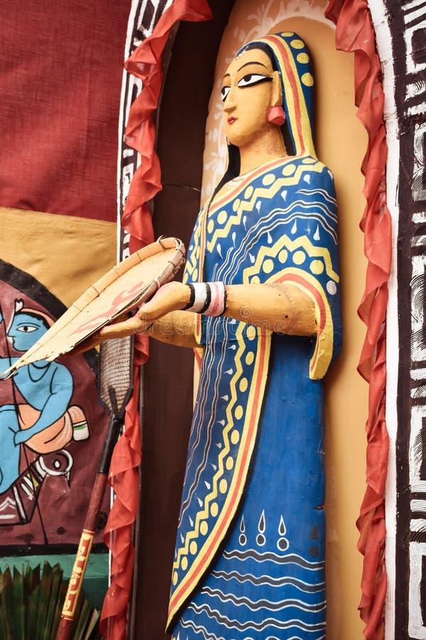 Bankura, Westbengalen, Indien, im Mai 2018 - Statue einer alten Stammes- Frauenstellung auf Hof mit einem Bambus lizenzfreies stockfoto