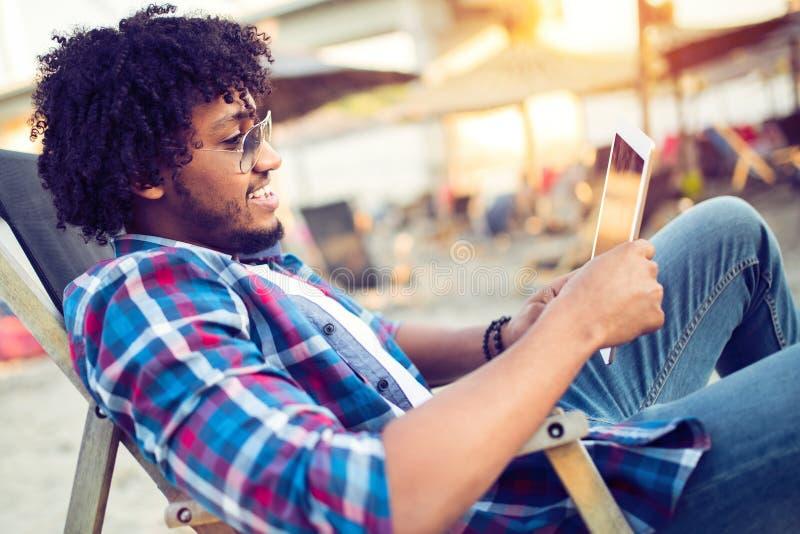 Bankwesen on-line, Porträt des glücklichen schwarzen Geschäftsmannes mit Tablette auf dem Strand stockbilder