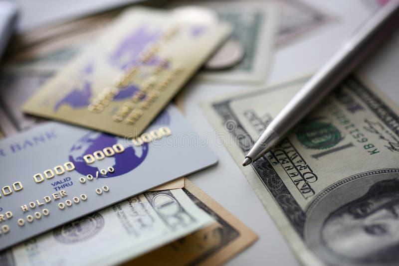 Bankwezen plastic kaart en zilveren pen die op grote hoeveelheid geld van de V.S. liggen royalty-vrije stock fotografie