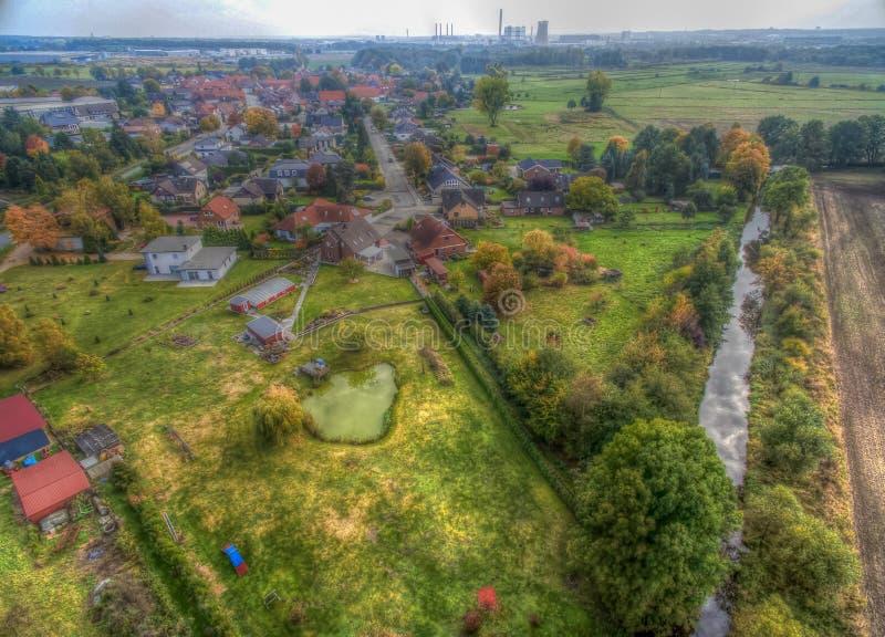 Banlieue d'une ville industrielle avec des prés et des pelouses en Allemagne du nord, courant redressé dans le premier plan, chem photo libre de droits