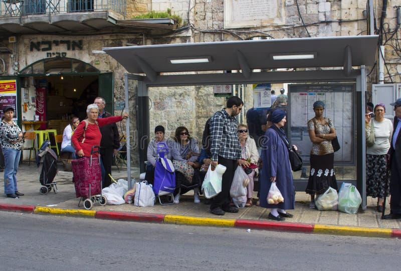 Banlieusards attendant un autobus dans un abri de bus local sur Shmuel Barukh Street près du marché en plein air de Mahane Yehuda photos libres de droits