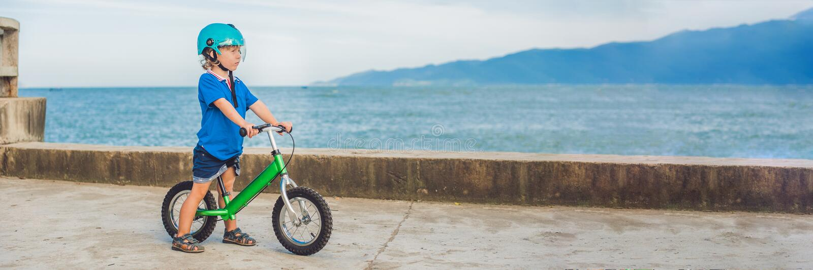 BANNER Active blond kid boy driving bicycle in the park near the sea. Toddler child dreaming and having fun on warm summer day. ou stock images