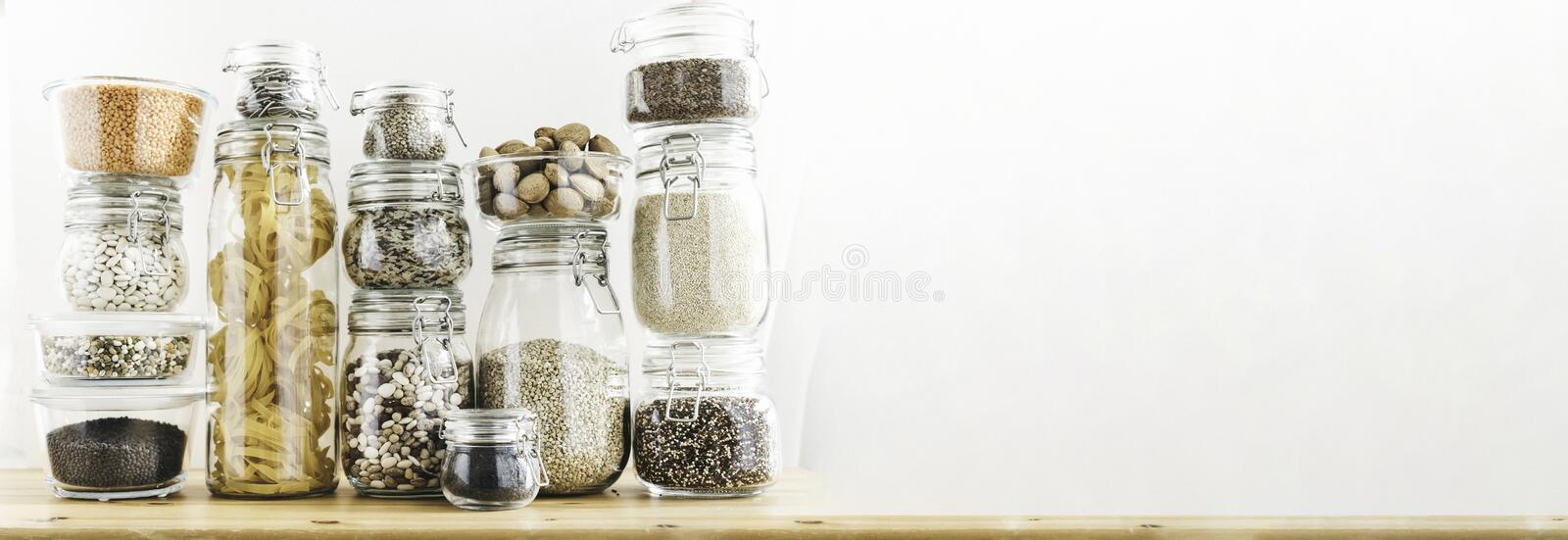 Banner with assortment of grain products and pasta in glass storage containers on wooden table. Healthy cooking, clean. Eating, zero waste concept. Balanced royalty free stock photos