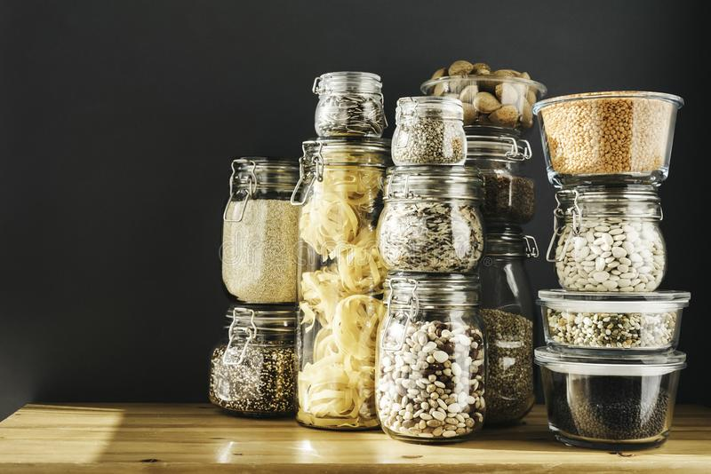 Banner with assortment of grain products and pasta in glass storage containers on wooden table. Healthy cooking, clean. Eating, zero waste concept. Balanced stock image