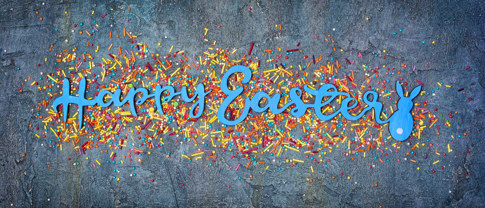 Banner with blue text of happy easter and sugar sprinkles or confetti as decor for bakery. Top view on bright text of happy easter with sugar sprinkles or stock photos