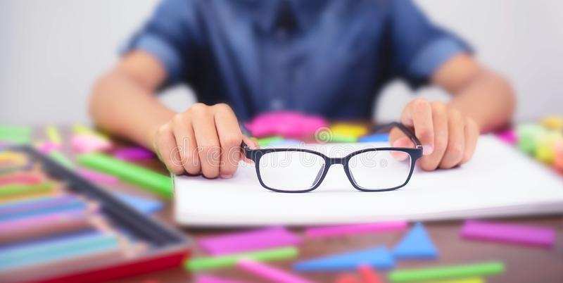 Banner boy holding glasses in their hands. Concept problem of ophthalmology correction of myopia. Concept back to school. Selective focus stock image