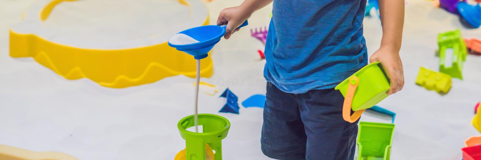 BANNER Boy playing with sand in preschool. The development of fine motor concept. Creativity Game concept long format. BANNER Boy playing with sand in preschool stock images