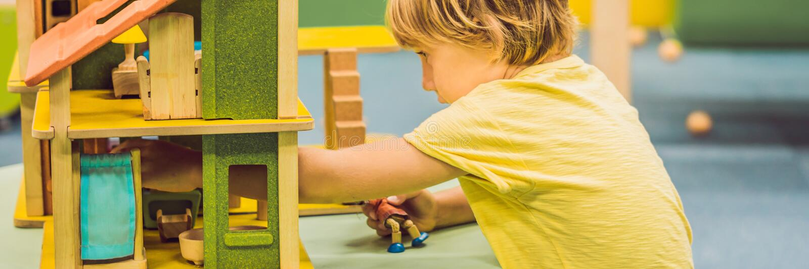 BANNER Boy playing with wooden house in kindergarten long format. BANNER Boy playing with wooden house in kindergarten. long format royalty free stock images