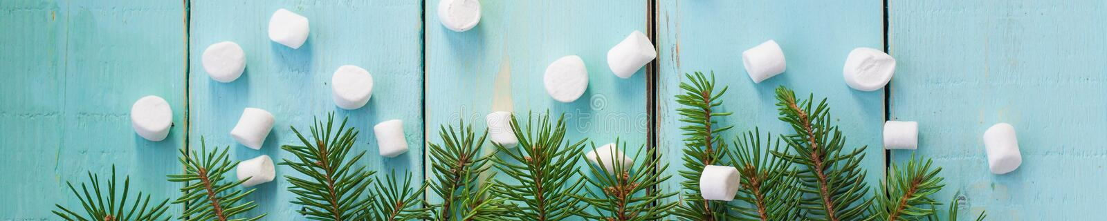Banner of Christmas border with branch of fir tree and marshmallows on wooden background stock photos
