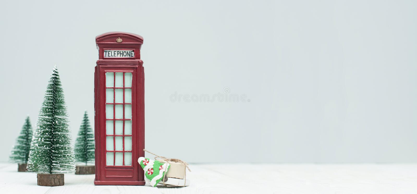 Banner with christmas decorations, toy red phone booth, trees, g stock photography