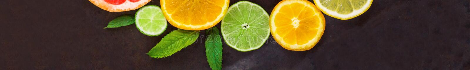 banner of citrus food pattern on white background - assorted citrus fruits with mint leaves on black background stock photo