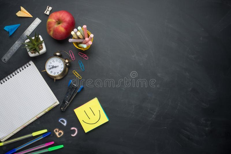 Banner concept Back to School Alarm clock, pencil Apple Notebook Stationery on blackboard background. Design Copy Space accessorie. S Top View Flat Lay royalty free stock photography