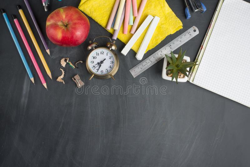 Banner concept Back to School Alarm clock, pencil Apple Notebook Stationery on blackboard background. Design Copy Space accessorie. S Top View Flat Lay royalty free stock image