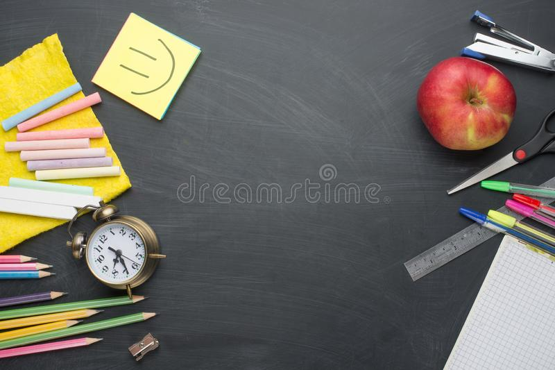 Banner concept Back to School Alarm clock, pencil Apple Notebook Stationery on blackboard background. Design Copy Space accessorie. S Top View Flat Lay royalty free stock photos