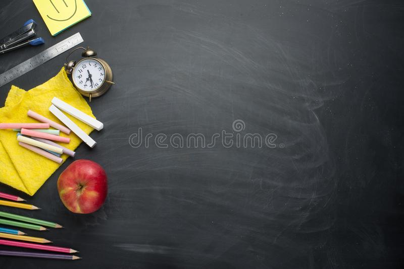 Banner concept Back to School Alarm clock, pencil Apple Notebook Stationery on blackboard background. Design Copy Space accessorie. S Top View Flat Lay stock photo